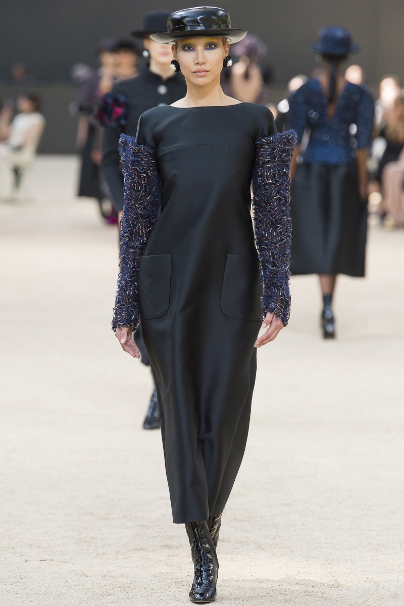 Model walking down runway at Chanel fall 2017 couture show in black dress with sequin sleeves