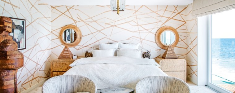 Bedroom with gold geometric pattern wallpaper with white bed