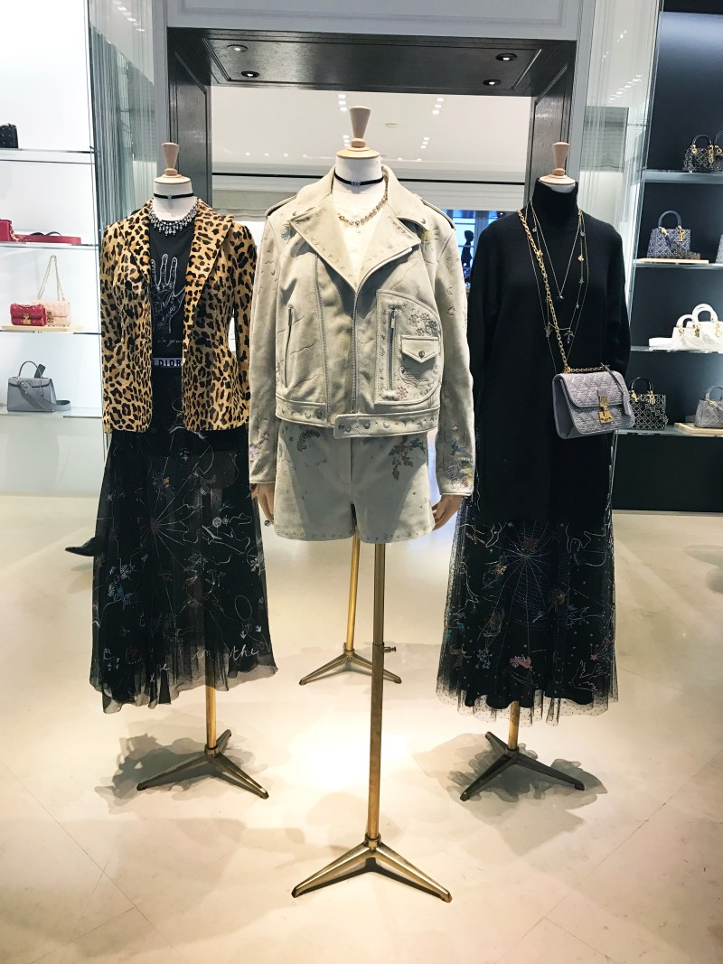 Three mannequins in the dior store wearing a leopard jacket, tulle embroidered skirt, suede jacket and shorts and a black dress with a dior purse