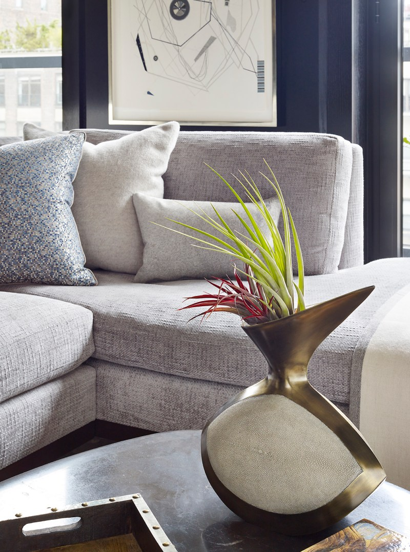 Close up detail photo of living room designed by Joe Lupo VT Home featuring grey custom chenille sectional sofa, throw pillows, fabric by pierre frey and robert allen, artwork on wall from Johannes vogt gallery, halston marble on custom cocktail table, brass and shagreen sculptural vase with greenery.