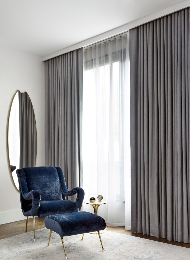 Image of interiors magazine spread featuring Joe Lupo VT Home. Image features a corner in a master bedroom with a blue velvet arm chair and foot rest, oval mirror, grey drapery and gold side table with clock.