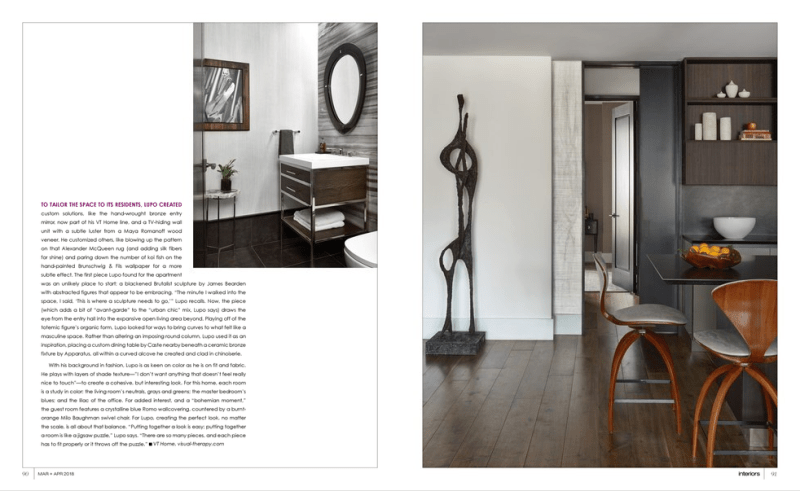 Image of interiors magazine march 2018 spread featuring Joe Lupo, founder of VT Home. Powder room pictured in the photo with an oval mirror, gray marble wall, sink, art on wall and side table. In the other photo is a african sculpture, walnut antique chairs, bowl with oranges on kitchen island, styled shelves and hallway leading to other room.