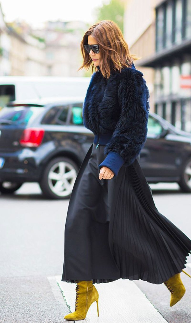 Street style shot of woman wearing statement booties , skirt and sweater