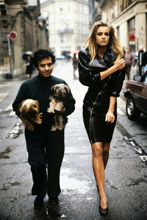 Azzedine Alaia walking down street with model and dogs
