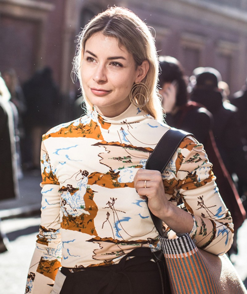 street style shot of girl wearing statement earrings, a celine mockneck and celine bag at london fashion week