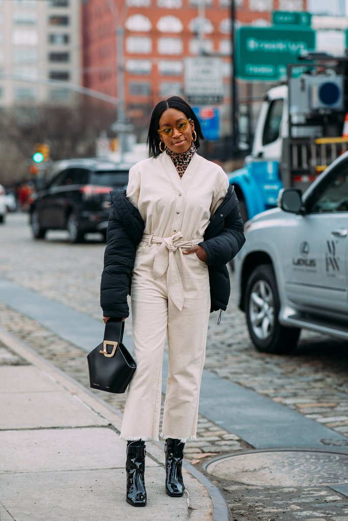 street style shot of a blogger walking and carrying a danse lente bag wearing a cream and white outfit