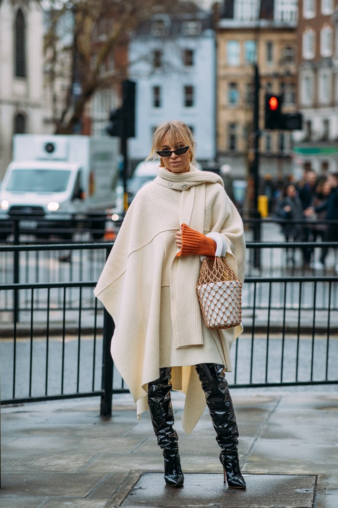 Street style shot of fashion editor carrying staud bag and wearing cream poncho, orange gloves, black boots
