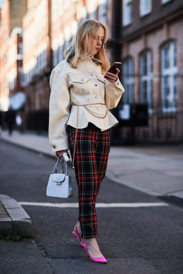 Street style shot of blogger attending london fashion week wearing a beige denim jacket with corset, plaid pants and kitten heels