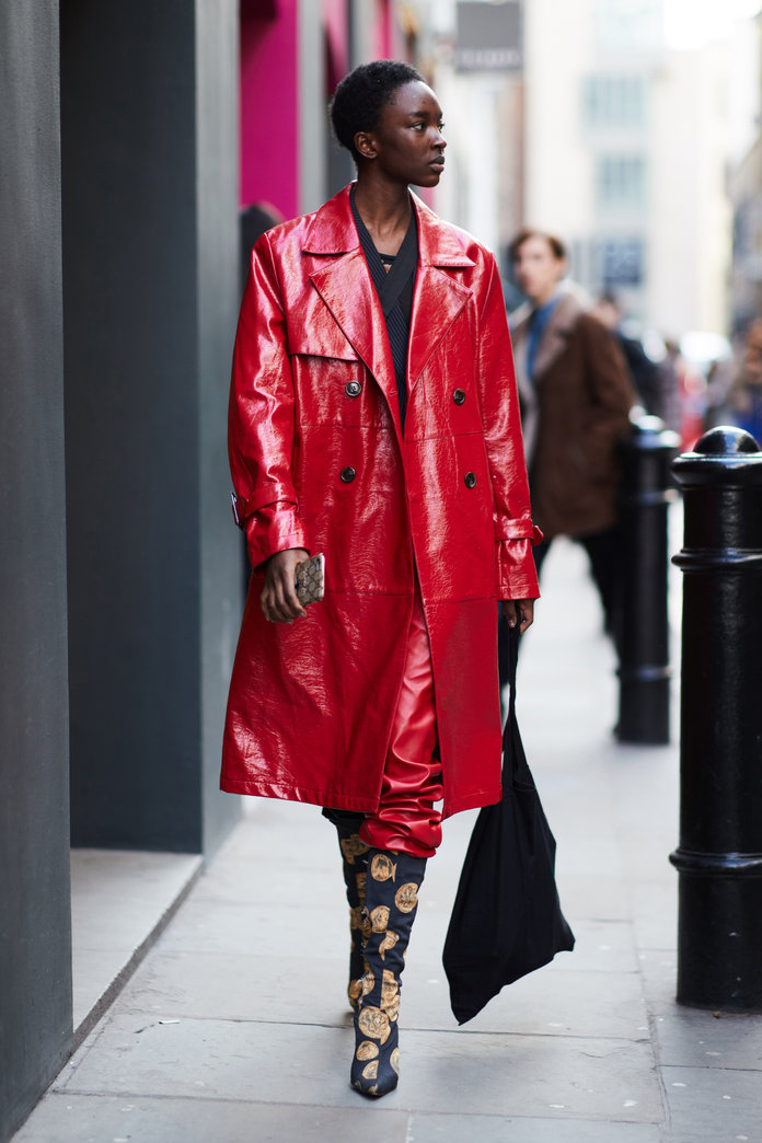 Street style shot of a blogger attending london fashion week wearing a red patent leather trench coat