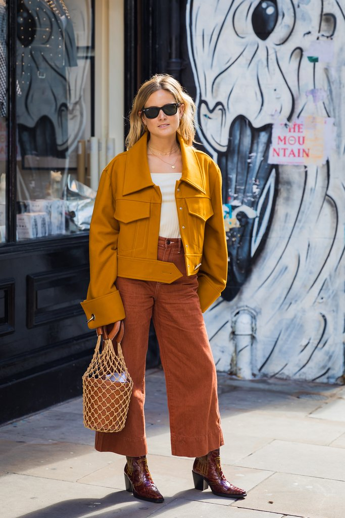 street style shot of girl wearing a mustard Jacket, Burnt Orange Pants and carrying a staud moreau bucket bag at fashion week