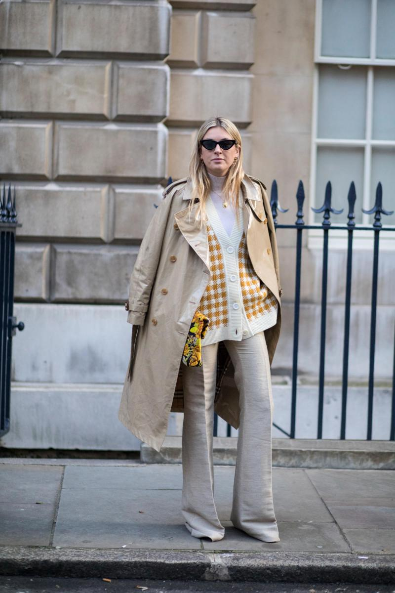 Street style shot of blogger attending london fashion week wearing a nude patent leather trench, beige pants and yellow check top