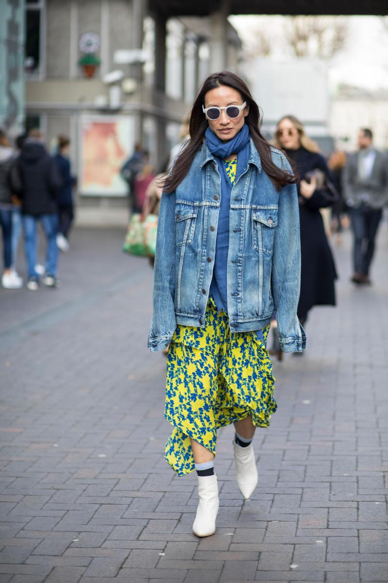 Street style shot of blogger at london fashion week in denim jacket, print skirt and white booties