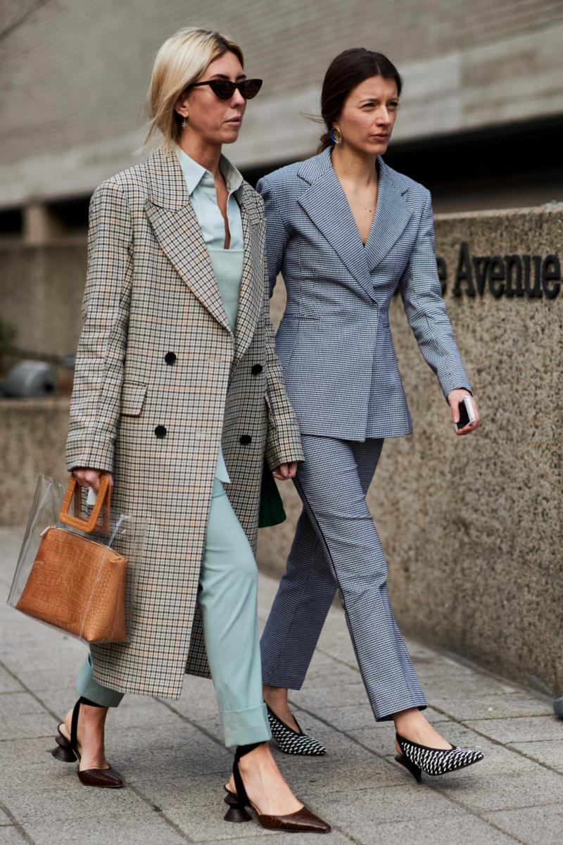 Street style shot of bloggers attending London fashion week in a plaid coat, green pants and shirt. other girl in a plaid suit