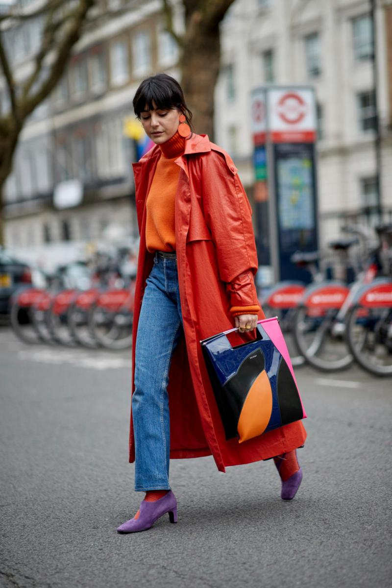 Street style shot of blogger attending london fashion week wearing a red jacket, orange turtleneck, jeans and large circular red earrings