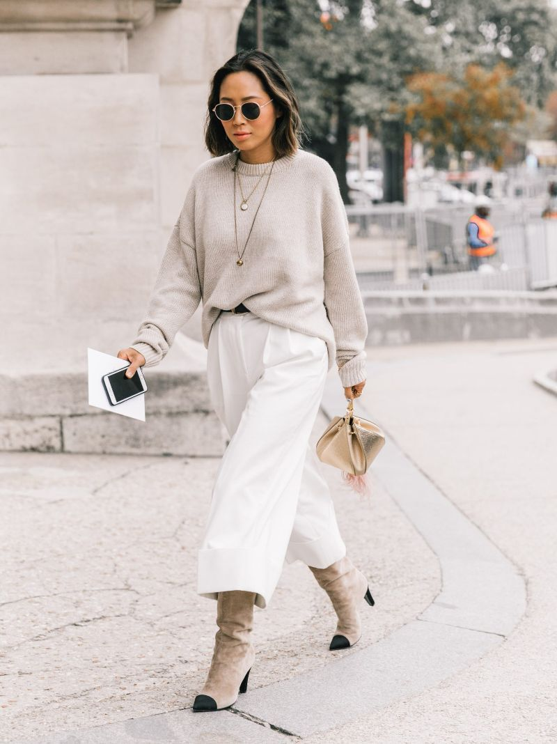 street style shot of a woman wearing a neutral outfit - beige and olive skirt