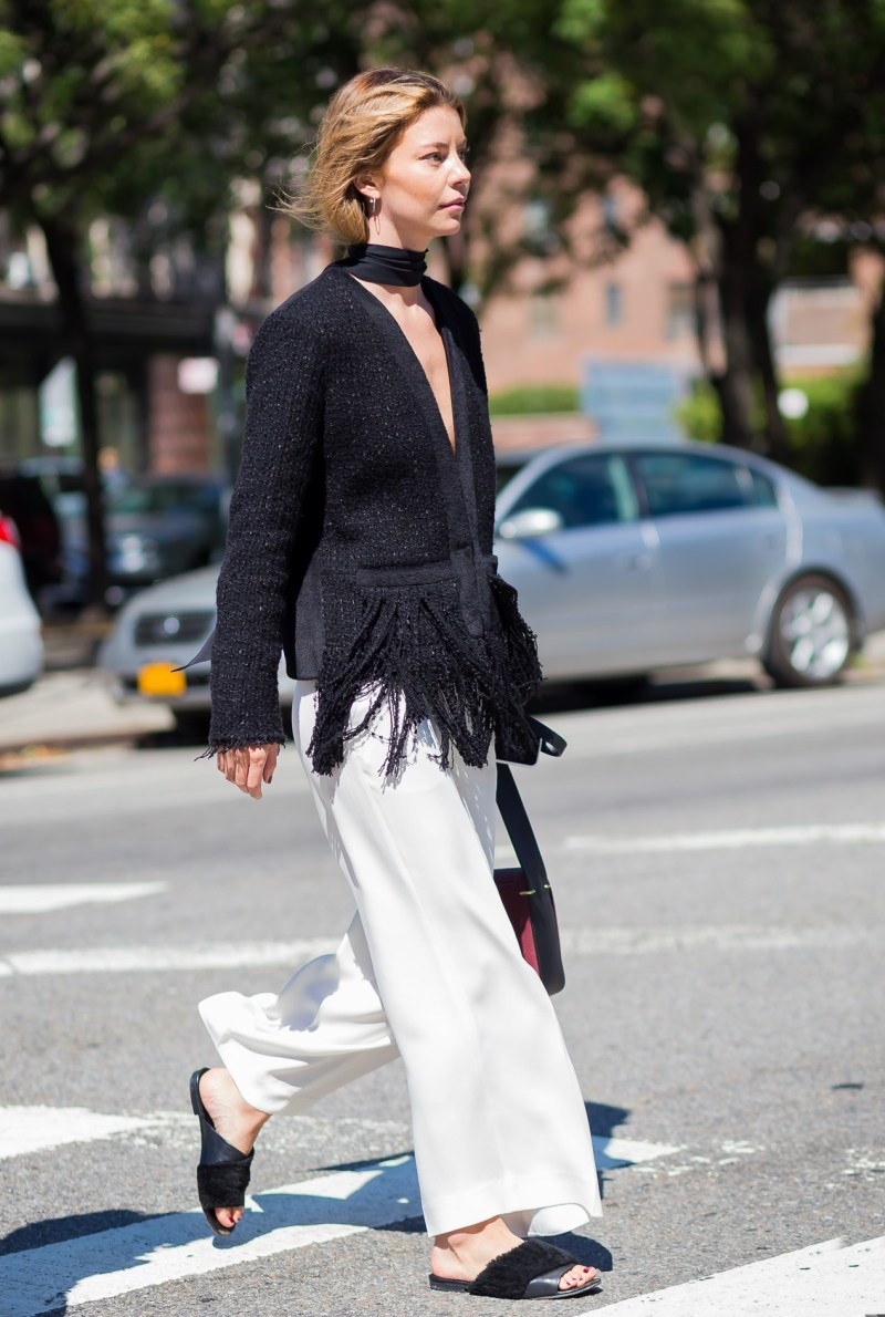 Street style shot of Annina Mislin wearing a black top, white pants and black slides
