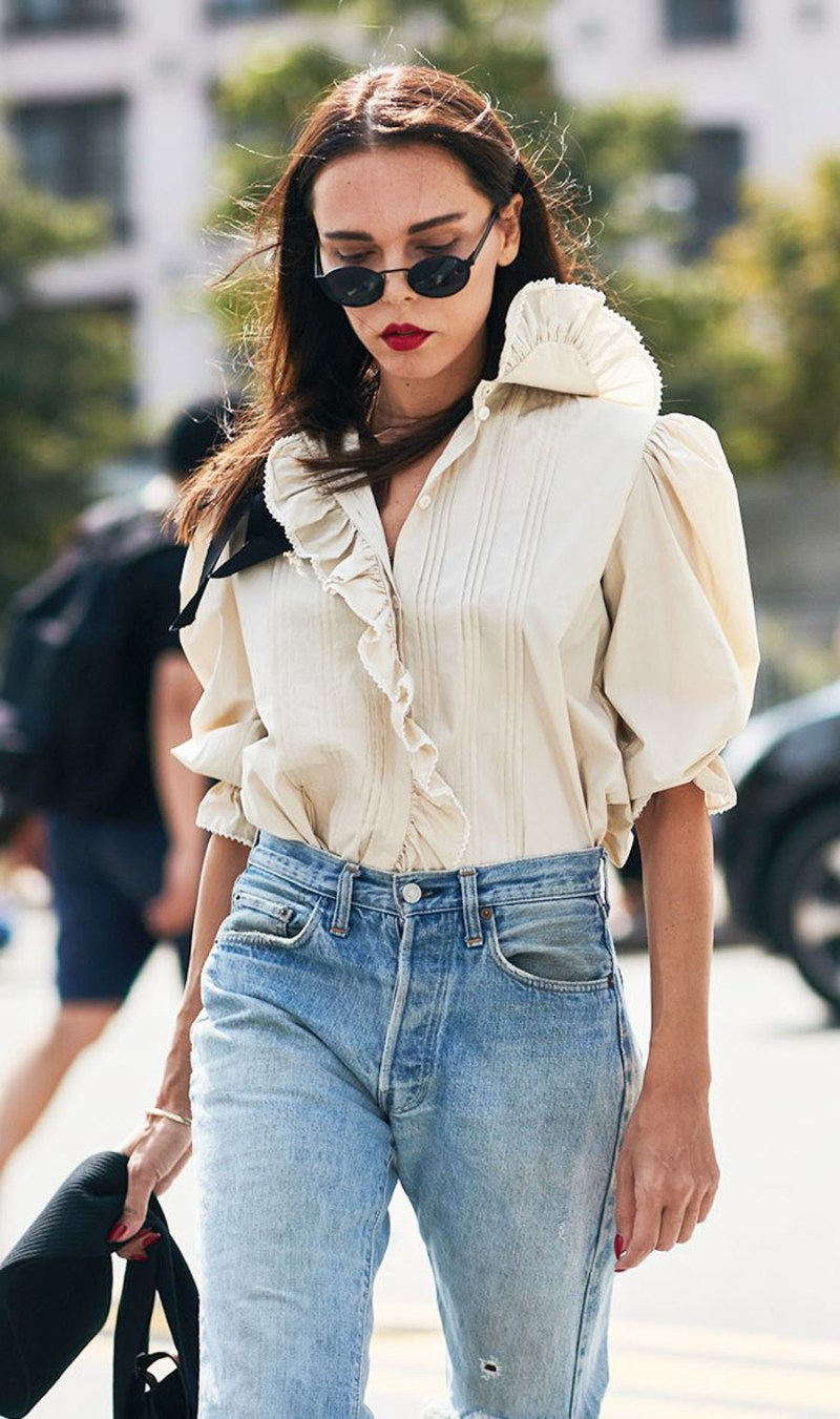 Street style shot of girl wearing flowy romantic blouse, small sunglasses, red lip stick and jeans