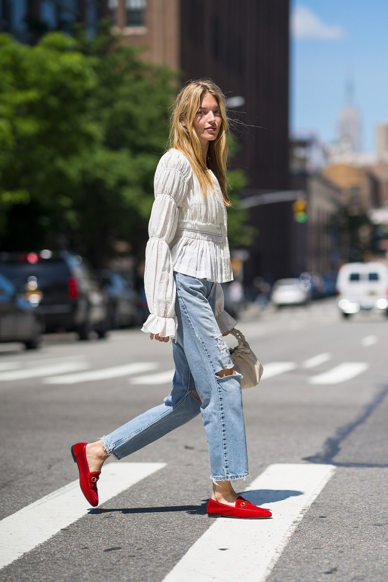 street style shot at fashion week of blogger in red gucci loafers, jeans and a white flowy top