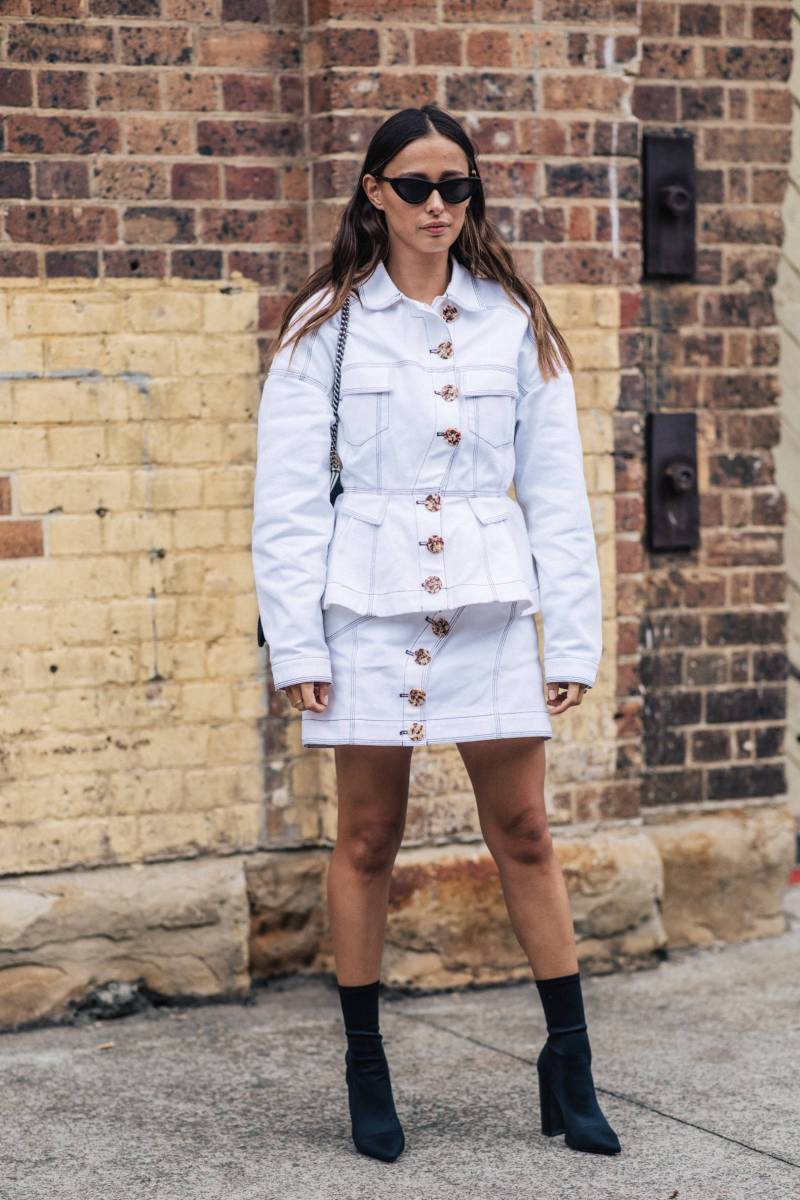 street style shot of blogger in a white denim two piece skirt and hacket with large buttons