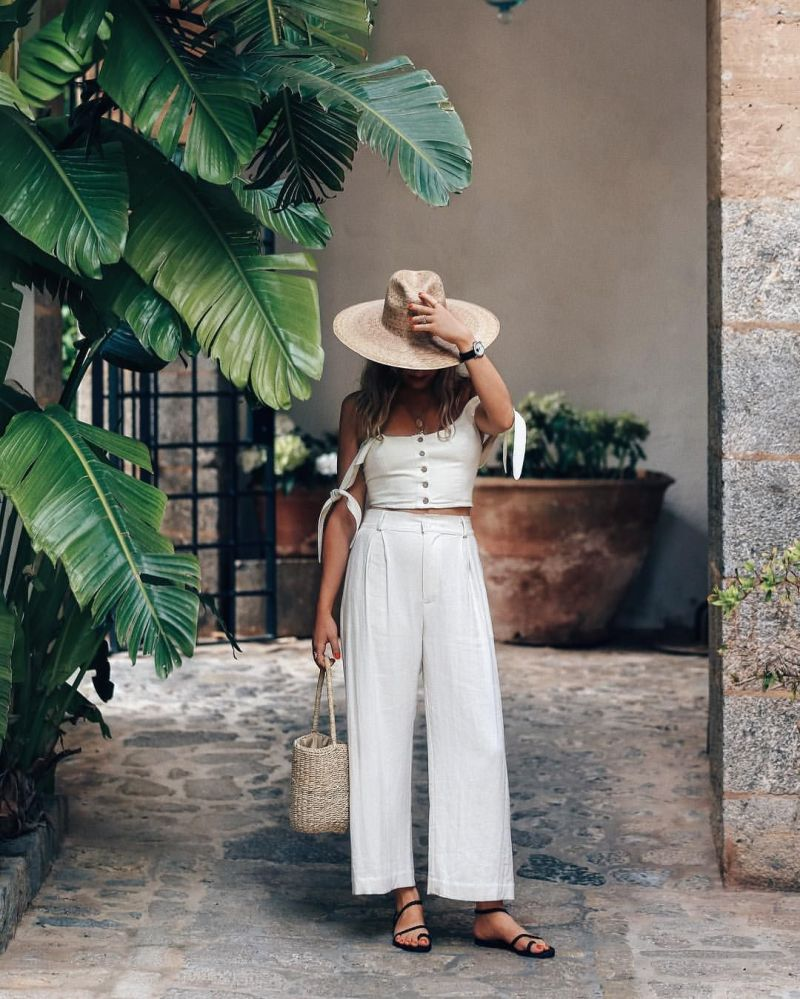 Photo of girl on vacation wearing a white two piece set and hat