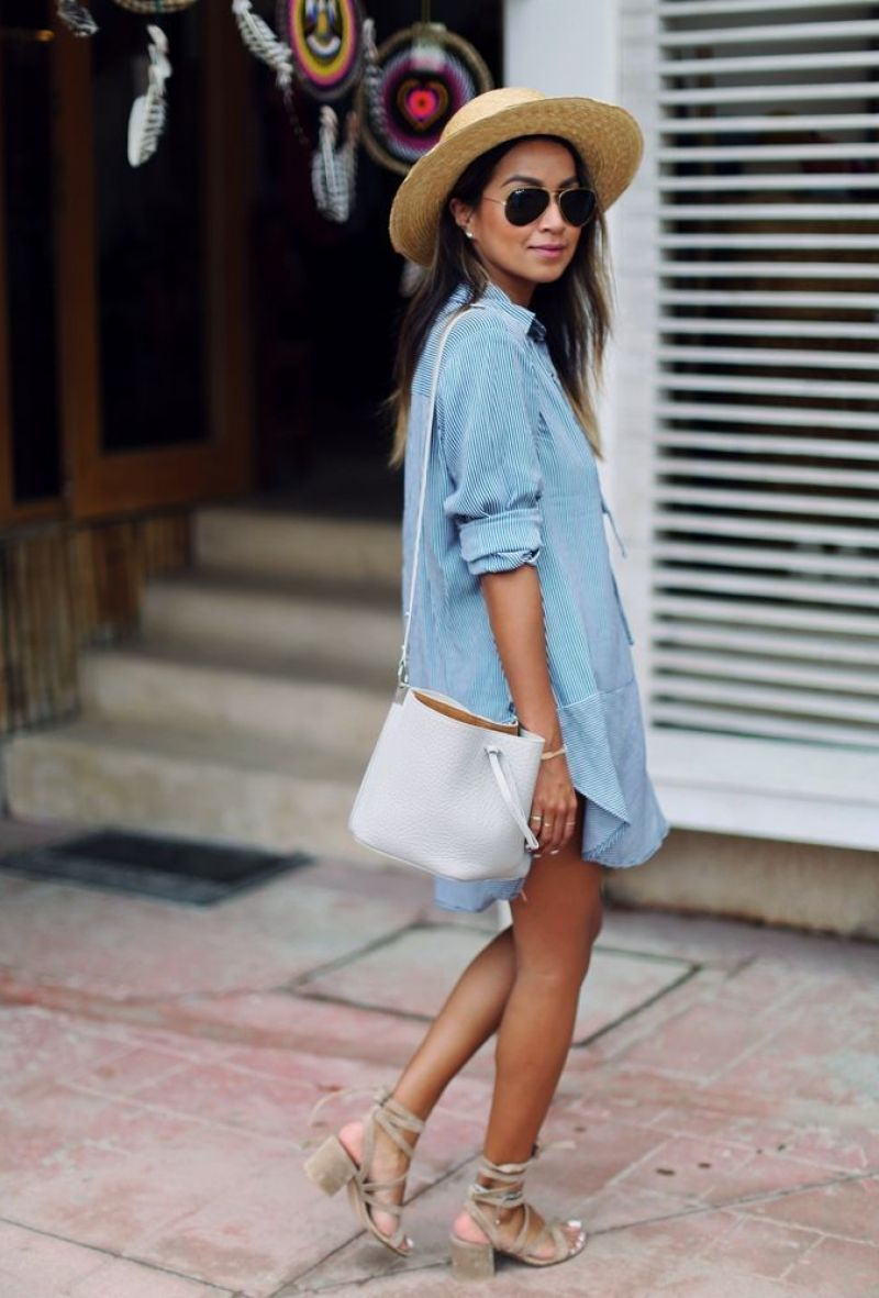Photo of blogger sincerely jules on vacation wearing a blue shirt dress, white bucket bag and sandals