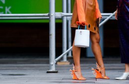 Image of two girls talking on a street in new york city wearing prada orange flame heels, a orange dress and white bag