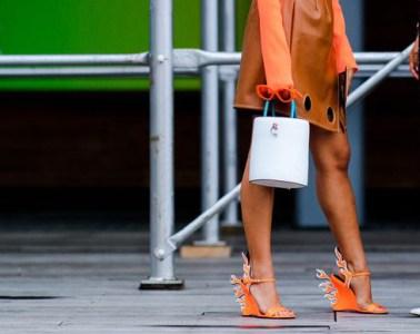 Image of two girls talking on a street in new york city wearing prada orange flame heels, a orange dress and white bag
