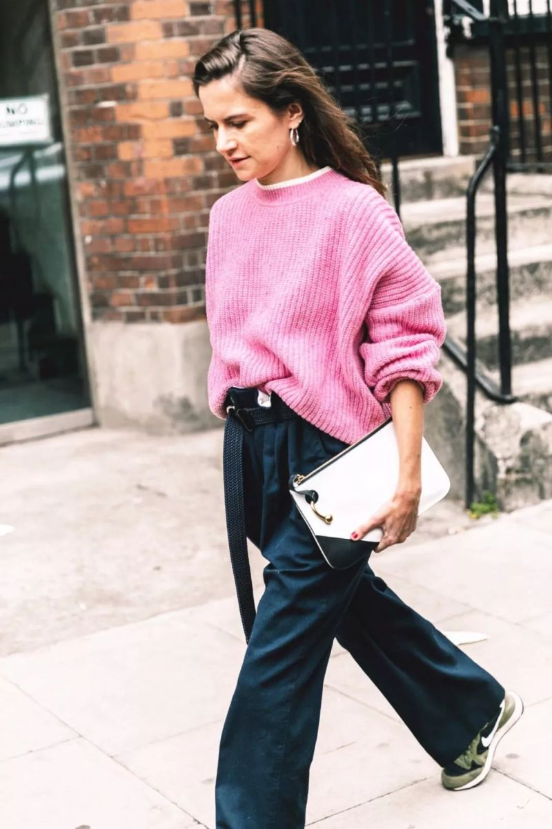Street style shot of girl wearing pink sweater and jeans