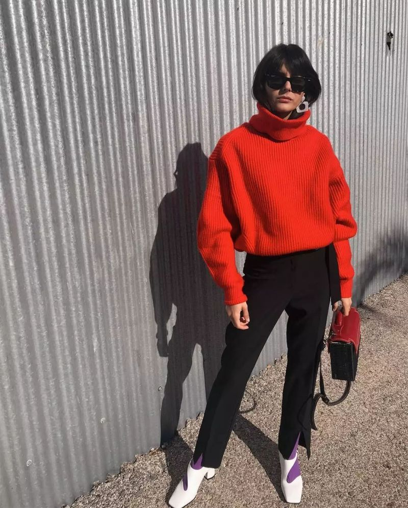 Girl wearing tomato red chunky knit sweater and black pants