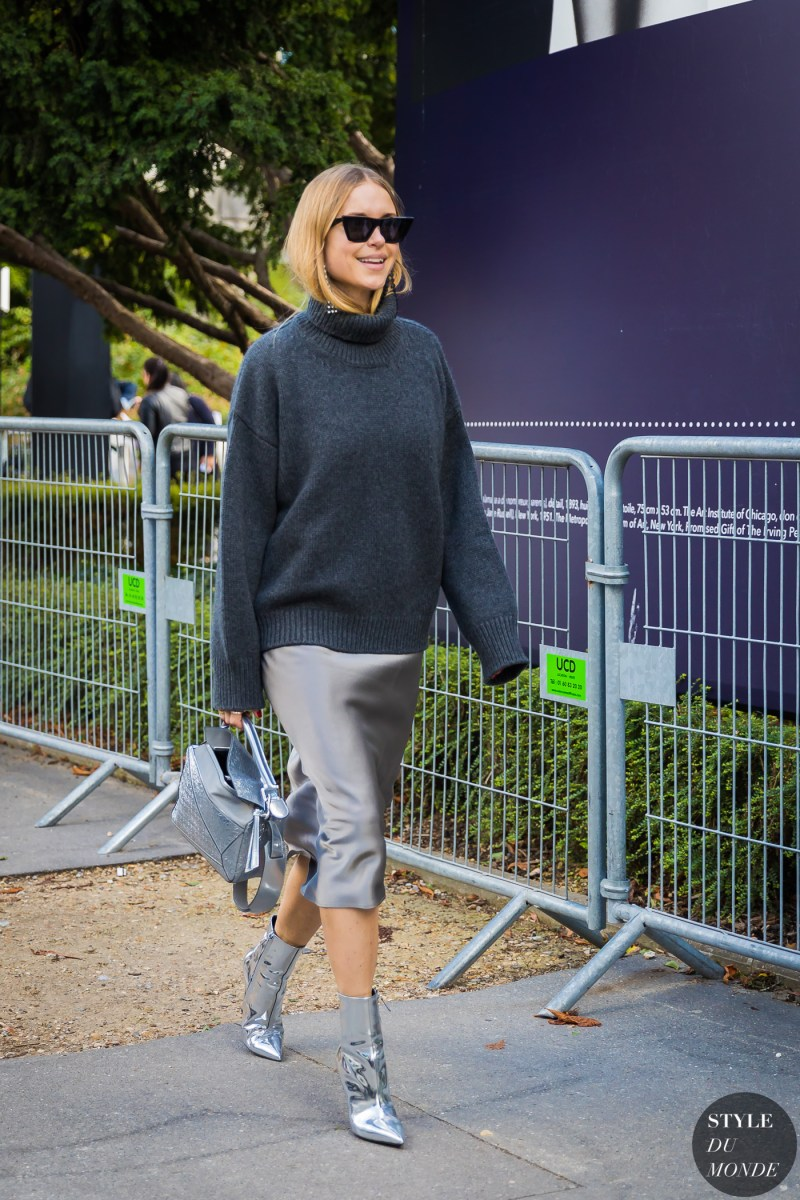 Pernille-Teisbaek in a grey sweater, silver midi skirt, metallic booties and carrying a silver loewe bag