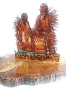 sculpture featuring two figures made of wood in red and yellow colors