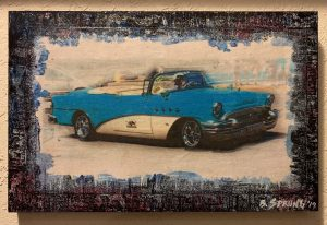 a blue vintage car driven by a person in a hat with painted boarder