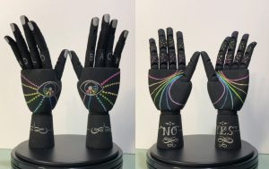 Two sculptures of hands, black with rainbows and it spells out hold back on the fingers
