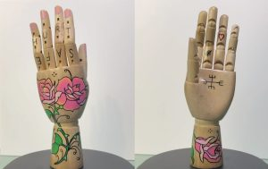 A pair of painted mannequin hands with flowers on them and letters spelling out SAFE and HURT on the fingers