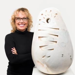 Susan Budge, smiling in a black turtleneck, standing next to one of her works, a large egg-shaped off-white form with asymmetrical cuts in the surface.