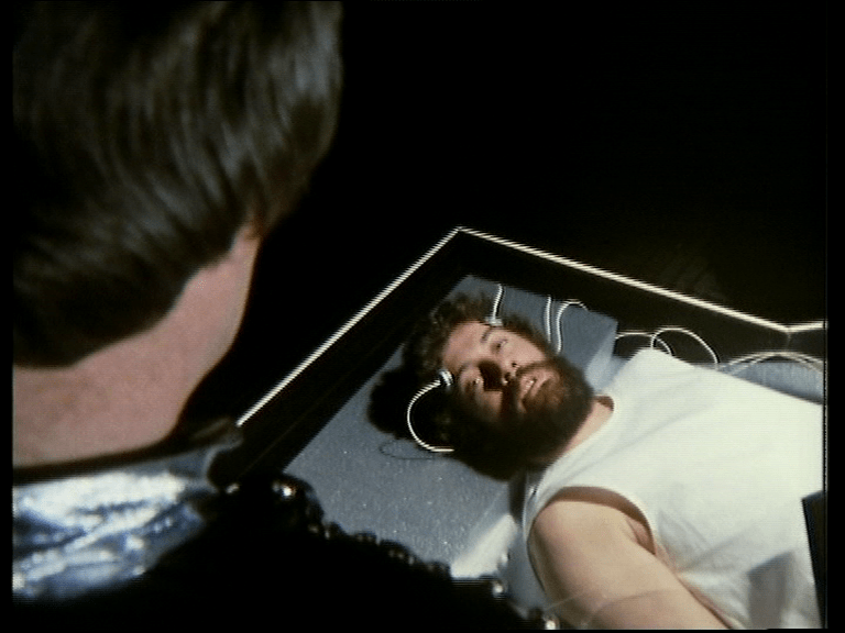A bearded Blake lying down, hooked up to wires, staring up at Avon