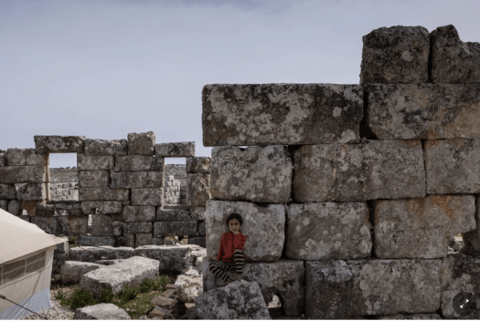 Young girl sitting in front of a wall of large, old, stones.