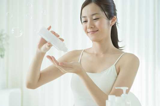 Young woman getting lotion to hand
