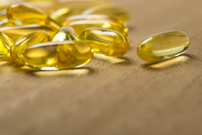 Pile of fish oil omega 3 gel capsules on wooden board