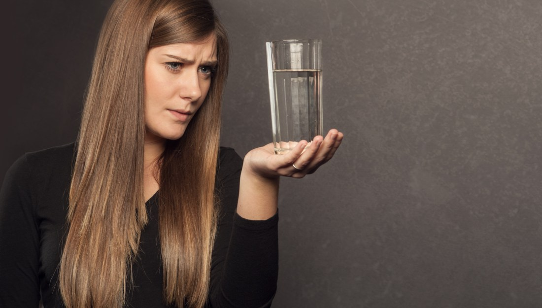 photo of woman looking at glass of water