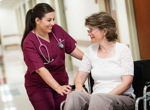 photo of nursing student talking to older patient