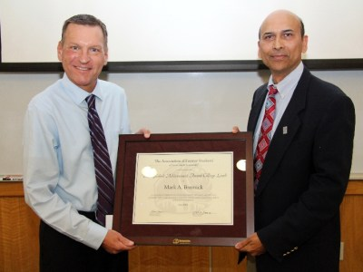 Indra K. Reddy, Ph.D., professor and founding dean of the Texas A&M Health Science Center Irma Lerma Rangel College of Pharmacy, presents to Mark Bremick, B.S. Pharm., instructor, The Association of Former Students Distinguished Achievement Award for college teaching on Aug. 22.