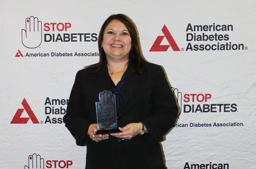 Starr Flores, Director of the Texas A&M Coastal Bend Health Education Center, holds the ADA LEARN award
