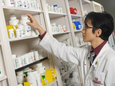 Pharmacy student reaching for bottle of pills.