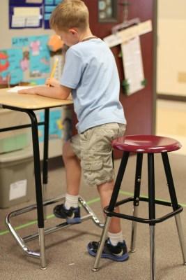Boy standing at desk