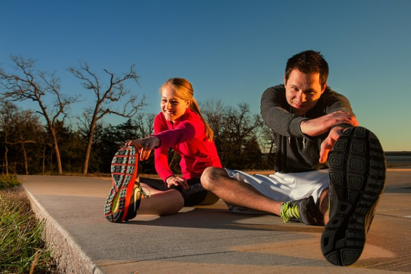 Woman and man sitting together on a sidewalk and stretching their hamstrings.