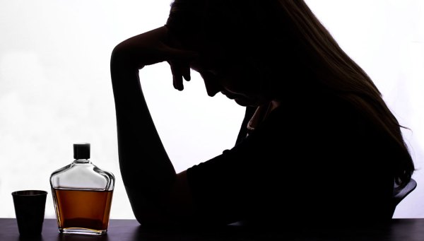 Woman with alcohol and shot glass holding her head in hands