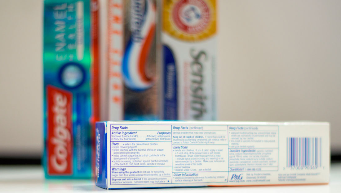 Toothpastes in the background with a closeup on the ingredients list .