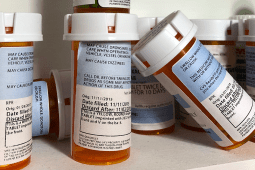 A close-up image of prescription pill bottles in medicine cabinet
