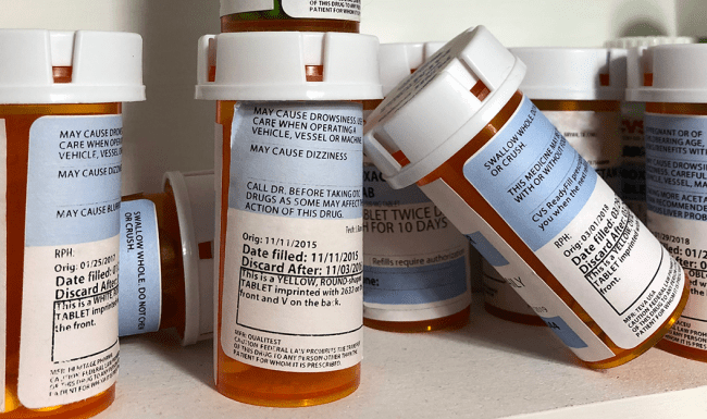 A close-up image of prescription pill bottles in medicine cabinet
